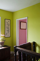View from the simple green-painted landing into a pink bedroom