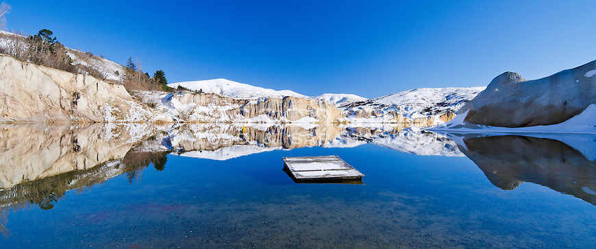 A perfect reflection of clay cliffs in the Blue Lake, St Bathans on a sunny blue sky winters day with pontoon on the lake. New Zealand - stock photo, canvas, fine art print