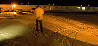 a gas worker walks through teh cold Wyoming night outside dormitory trailers at a man camp that houses Halliburton employess some 20 miles south of Pinedale, Wyo., Thursday, March 2, 2006. (Kevin Moloney for the New York Times)