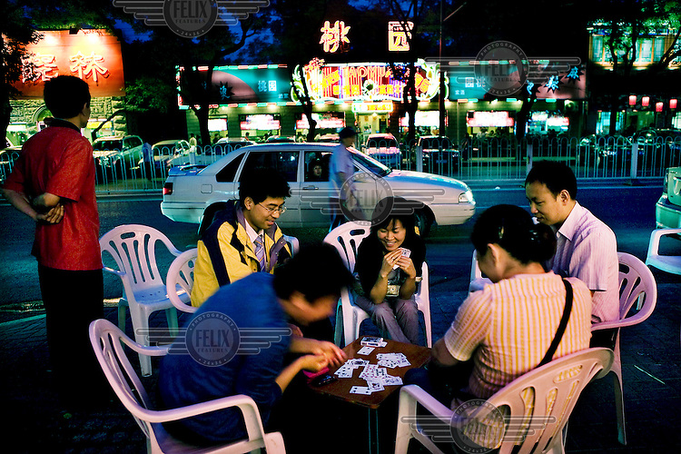A group of friends play cards while waiting for a table in a restaurant on the Dongzhimenwai Dajie in central Beijing.