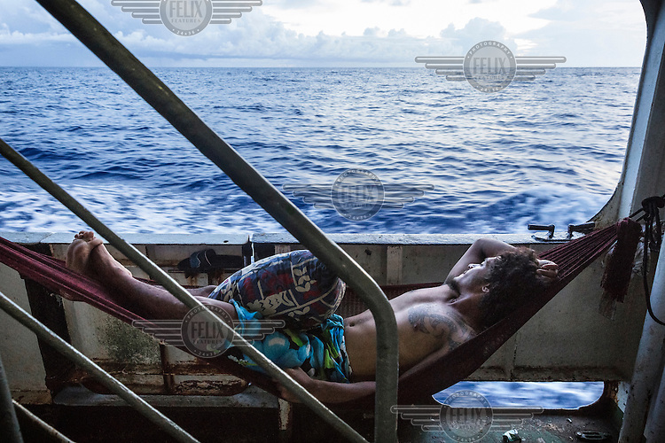 A crew member rests in a hammock strung onboard the 'Manu Folau' as its plys the inter-island routes to Nui Island in Central Islands Group of Tuvalu. The island nation has only two ships, the 'Manu Folau' and the 'Nivaga II', that travel between the outer islands (which are accessible only by boat) transporting goods and passengers.