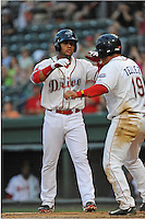 Second baseman Yoan Moncada (24) of the Greenville Drive, left, slaps hands with Francisco Tellez (19) after both scored in a game against the Lexington Legends on Monday, May 18, 2015, at Fluor Field at the West End in Greenville, South Carolina. Moncada, a 19-year-old prospect from Cuba, made his professional debut tonight in the Red Sox organization. (Tom Priddy/Four Seam Images)