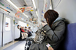 A young woman applies makeup on a train in Tokyo, Japan.