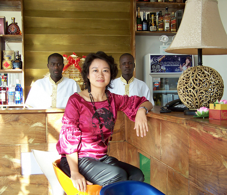 Benin / Cotonou / 6.6.2009 /  Meiyun Long is 34 years old and a Chinese entrepreneur. She arrived in Benin for the first time in 2002, and then returned again and again, running different types of businesses. Since 2004 she has stayed in the country. Meiyun is shown here in the restaurant that she currently runs. The Jasmin restaurant was set up all by herself in two months: you can see here that the African waiters are wearing traditional Chinese costumes, directly imported, just like everything else in the restaurant. Speaking about her migration, she says that &ldquo;it&rsquo;s hell in China. It&rsquo;s not about a political thing, it&rsquo;s about China&mdash;it&rsquo;s really crowded and stressful, and brutally competitive. I can breathe here. It&rsquo;s much more relaxing, and you can always find a solution to any problem.&rdquo; (Jasmin Resturant, Cotonou, Benin. June 2009)<br /> <br /> &copy; Giulia Marchi