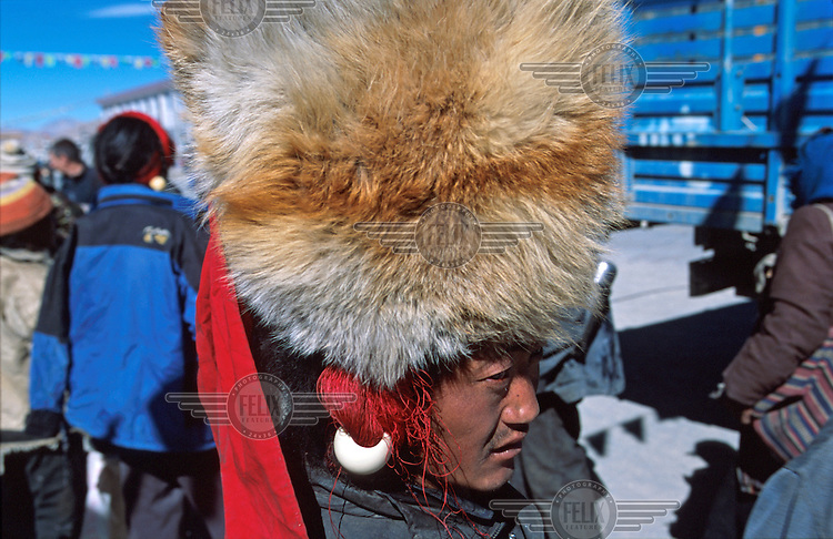A Khampa man wearing a large foxskin hat along the main street in town of Tingri on the Tibetan Plateau. Tingri is a popular market town, and many travel in from the surrounding rural areas.