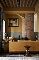 The sofas in the seating seating area are upholstered in an ochre yellow fabric to match the walls. A brick tiled fireplace is built into one corner.