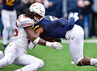 Morgantown, WV - NOV 18, 2017: West Virginia Mountaineers running back Kennedy McKoy (4) runs through the tackle of Texas Longhorns linebacker Malik Jefferson (46) during game between West Virginia and Texas at Mountaineer Field at Milan Puskar Stadium Morgantown, West Virginia. (Photo by Phil Peters/Media Images International)