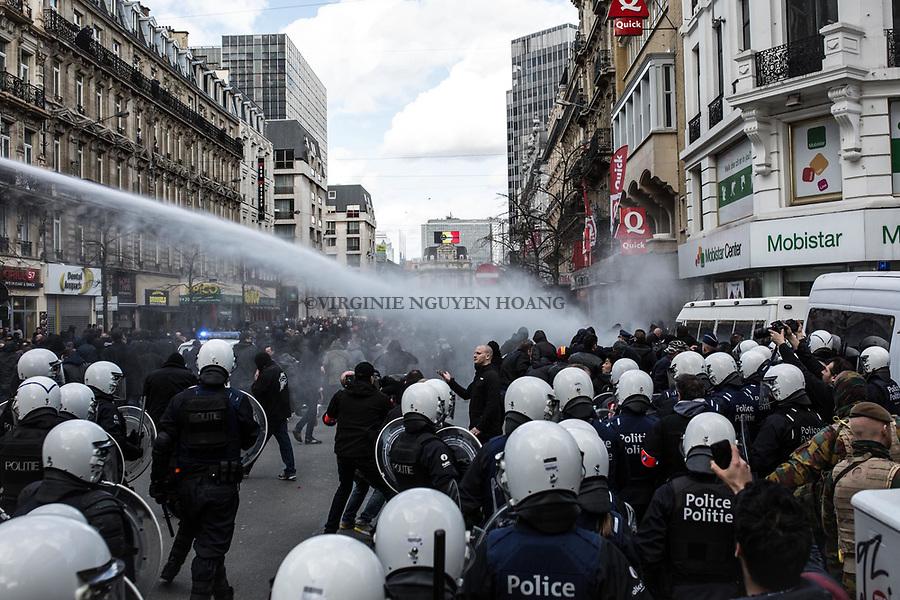 BRUXELLES,Belgique: La police évacue les hooligans vers la Gare du Nord à l'aide de pompe à eau, le 27 mars 2016. Peu après 14h, environ 400 hooligans sont arrivés à la Bourse et on semé le trouble au mémorial aux victimes des attentats de Bruxelles. Après 45min, la police est entrée en action pour encercler les individus et les repousser jusqu'à la gare du Nord.