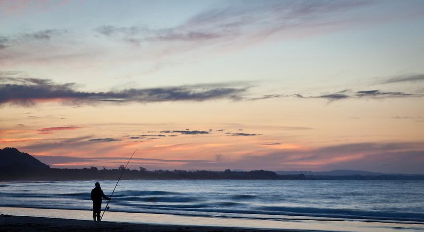 Firsheman at sunset at Opapae Bay, North Island, New Zealand