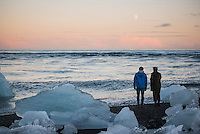 Father and son walking on Jokulsarlon Beach, a black volcanic beach at sunset, South East Iceland