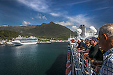 USA, Alaska, Ketchikan, passengers watch from deck as the cruise ship departs Ketchikan through the Clarence Straight for Juneau