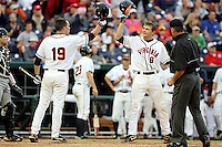 Virginia's Steven Proscia (19) and John Hicks (8) celebrate Hicks' homerun in the fourth inning. South Carolina beat Virginia 7-1 at the 2011 College World Series on June 21 in Omaha, Neb. (Photo by Michelle Bishop)..