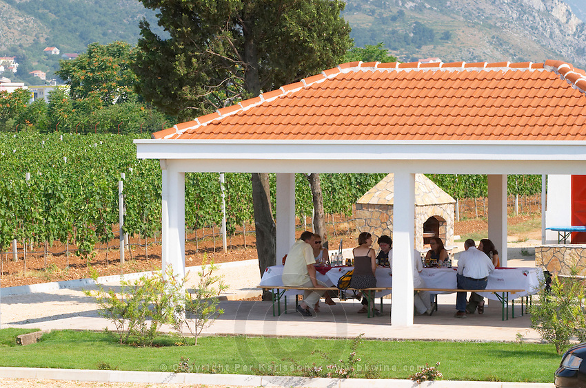Visitors tasting wines under a sun shade roof in the vineyard. Hercegovina Vino, Mostar. Federation Bosne i Hercegovine. Bosnia Herzegovina, Europe.