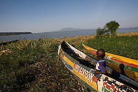 a young boy sitting in a fishing boat on the shres of lake victoria in Homa Bay, Kenya.
