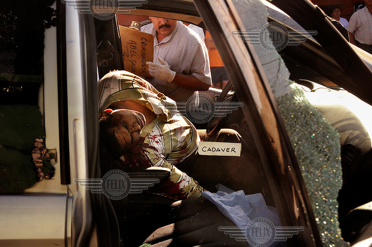 A murder victim lies in a truck as a policeman investigates. The death was probably linked with drug trafficking.