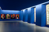 The blue walls and ceiling of this contemporary gallery bring an exhibition of photographic portraits to life