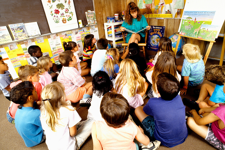 Teacher reading to class of second graders in circle on floor in schoo