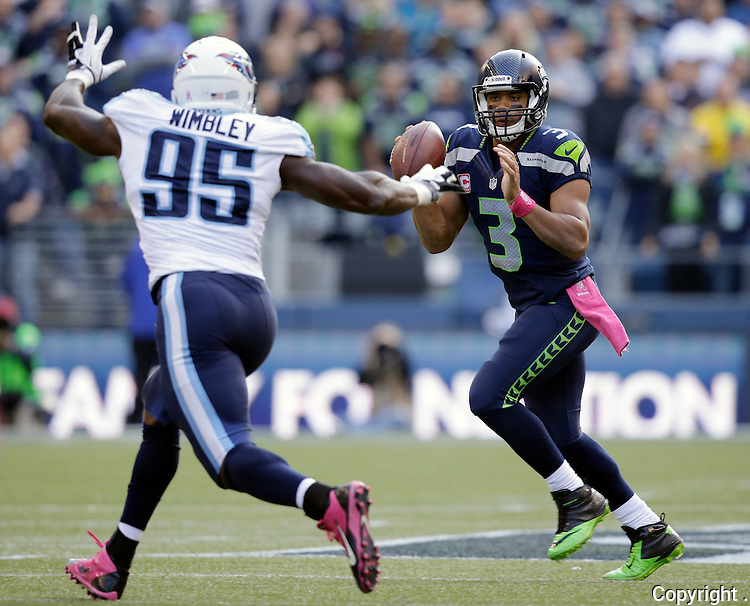 Seattle Seahawks quarterback Russell wilson, right, looks to pass while being chased by Tennessee Titans defensive end Kamerion Wimbley (95) in the third quarter at CenturyLink Field in Seattle, Washington on  October13, 2013.  Wilson completed 23 passes for 257 yards and rushed 61 yards in the Seahawks 20-13 win over the Titians.   ©2013. Jim Bryant Photo. All Rights Reserved.