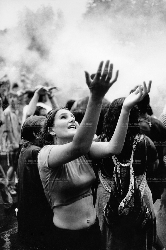 Switzerland. Zürich. A young woman dances with both her hands open to the sky during the Street Parade which is a yearly techno event in Zurich. The Street Parade is the most attended techno parade in the world and is the largest annual event in Zurich. Officially a demonstration for freedom, love and tolerance attended by up to a one million people, it proceeds along the side of Lake Zurich on the second Saturday of August. © 1995 Didier Ruef