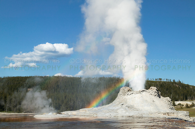 Castle Geyser erupting with a double rainbow in its mist in Yellowstone National Park, Wyoming, USA