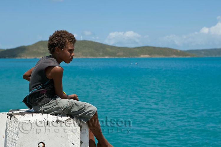 Torres Strait Islander boy fishing off the jetty at Horn Island, Torres Strait Islands, Queensland, Australia