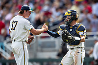 Michigan Wolverines pitcher Jeff Criswell (17) celebrates with catcher Joe Donovan (0) after recording a save against the Texas Tech Red Raiders during the first game of the NCAA College World Series on June 15, 2019 at TD Ameritrade Park in Omaha, Nebraska. Michigan defeated Texas Tech 5-3. (Andrew Woolley/Four Seam Images)