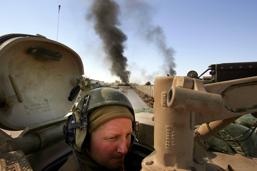 A tank crewman attached to 2nd Battalion 1st Marines peers out from the safety of his tank to survey his surroundings as the Marines continue with Operation Steel Curtain in Ubaydi, Iraq on Tues. Nov. 14, 2005.