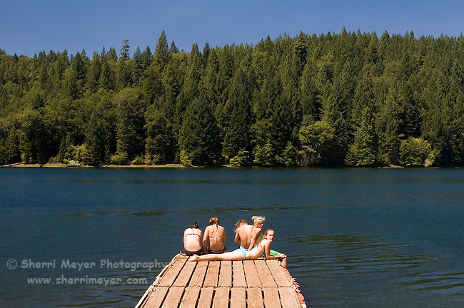 Teens hanging out on the end of a dock, Sugar Pine Reservoir, near Foresthill California