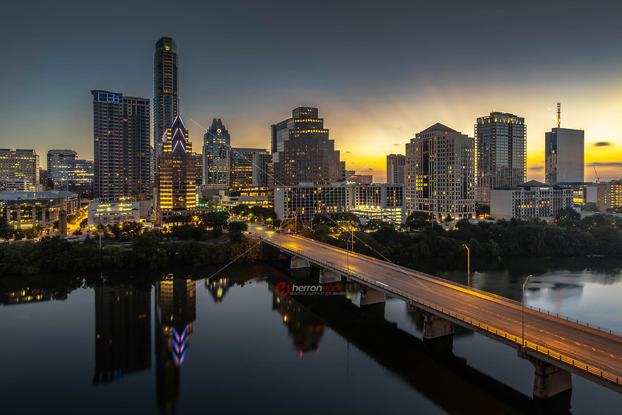 A glimmering sunrise shines through skyscrapers and the Congress Avenue Bridge amid the ever growing downtown Austin skyline in this image taken from atop of the Hyatt Regency Hotel. <br />