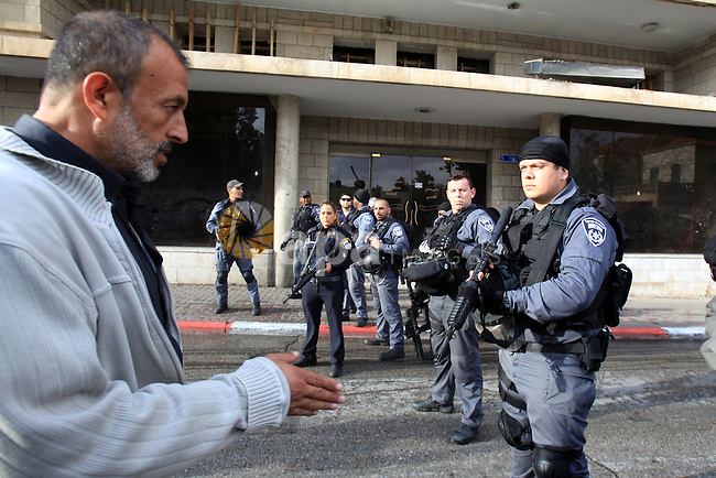 A Palestinian man walks past Israeli policemen outside a Jerusalem court, where is lader of the radical northern wing of the Islamic Movement in Israel, Sheikh Raed Salah was convicted on October 27, 2015. An Israeli court upheld a conviction of the firebrand Islamic cleric and jailed him for 11 months for inciting violence over Jerusalem's Al-Aqsa mosque in 2007. Photo by Mahfouz Abu Turk