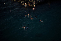 "Youths swim in the Gulf of Naples near rocks at a private ""beach"" on Thursday, Sept. 17, 2015, in Sorrento, Italy. (Photo by James Brosher)"