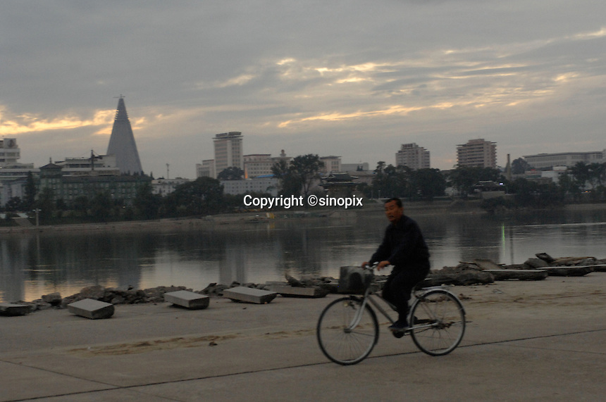 A cyclist pass the Taedong River in Pyongyang, North Korea. The Taedong River is a large river in North Korea. It rises in the Rangrim Mountains of the country's north. It then flows southwest into Korea Bay at Nampo. In between, it runs through Pyongyang. The river has a length of 450.3 kilometers.