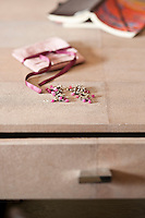 Detail of a pair of delicate silver earrings with pink gemstones on a leather covered writing table
