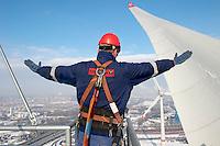 GERMANY Hamburg , Enercon windmill E-126 with 6 MW during Winter, service worker, port and skyline of Hamburg / Deutschland Hamburg , Enercon Windrad E-126 mit 6 MW in Altenwerder,  Service Mitarbeiter, Hintergrund Hafen und city skyline im Winter