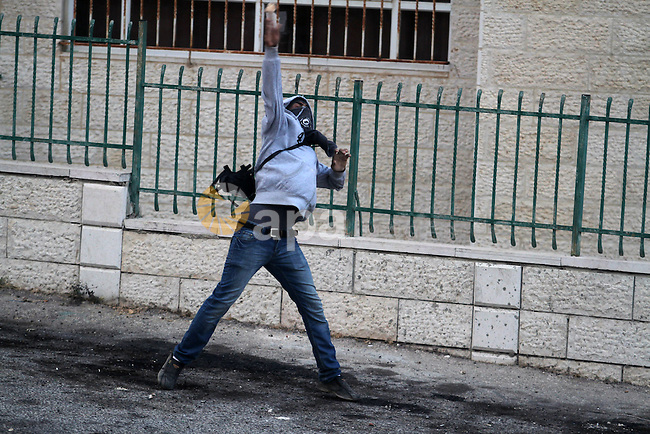 A Palestinian protester uses a sling to throw stones at Israeli soldiers during clashes near the Israeli military prison of Ofer, near the West Bank city of Ramallah October 4, 2013. Photo by Issam Rimawi