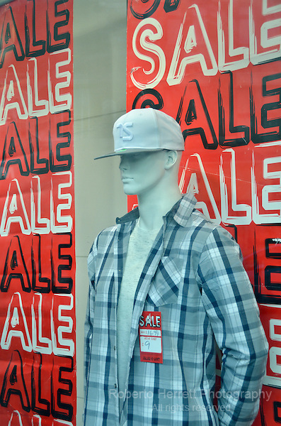 Mannequin and red sale sign in a UK High Street shop window.