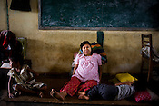 A pregnant woman is seen with her children in the shelter. Refugees from the Falan village in Kyauktan township take shelter in the Middle school that has been temporarily transformed as a refuge for 18 families and 140 people. .