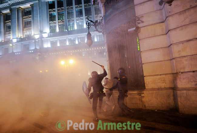 "Two riot police officers chase after a protester during clashes at the end of a demonstration organized by Spain's ""indignant"" protesters, a popular movement against a political system that they say deprives ordinary Spaniards of a voice in the crisis, near the parliament building in Madrid during a general strike on November 14, 2012.   (c) PEDRO ARMESTRE"