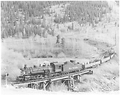 Fireman side view of K-36 #483 crossing a trestle just before a road crossing signal.<br /> D&amp;RGW  Monarch Branch ?, CO  Taken by Krause, John