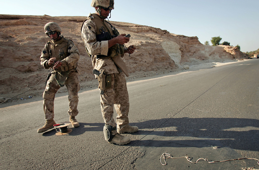 Marine explosive ordinance disposal techs attached to 3rd Battalion 1st Marines (3/1) mark an IED buried in the asphalt with a GPS device while preparing to set a high explosive charge to dislodge or destroy it. The device was discovered by a sweeping infantry foot patrol during  Operation River Gate - the search for insurgents and weapons in the Al-Anbar Province cities of Haditha, Haqlaniya, and Barwanah on Monday, Oct. 10 2005. Such sweeps have discovered dozens of IEDs since the operation commenced a week ago.
