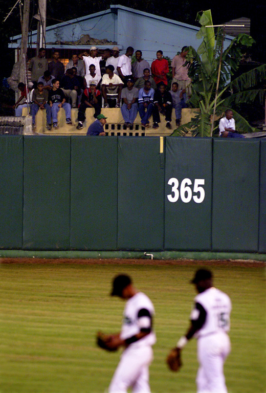 024212.SP.0117.domgame7.kc--San Pedro de Macor, Dominican Republican--Just past the outfield wall of Estadio Tetelo Vargas diehard baseball fans watch from houses that border the stadium. During this game Escogido plays Estrellas in the best-of-seven series.