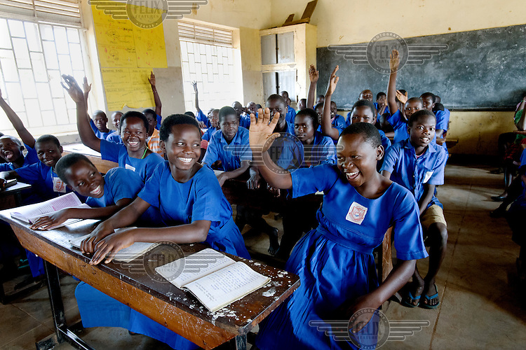 Girls raise their hands in response to the question, 'Who uses Afripads?' at Aputiri Primary School.