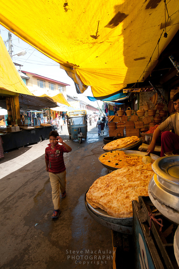 Massive fried puris (puffed breads) and other vegetable dishes for sale in covered outdoor market, Hazratbal area, Srinagar, Kashmir, India.