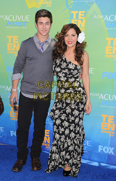 David Henrie & Maria Canals-Barrera.The Fox 2011 Teen Choice Awards held at Gibson Ampitheatre in Universal City, California, USA..August 7th, 2010.full length hand on hip black white grey gray one shoulder dress flower in hair jeans denim jumper sweater.CAP/ROT/TM.©Tony Michaels/Roth Stock/Capital Pictures