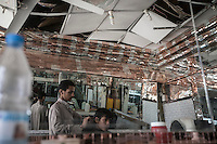 Wednesday 15 July, 2015: A Houthi fighter teenager attends a barbershop damaged by a bomb blast on the day before Eid in one downtown street of Sa'dah, a city subdued to heavy bombarments carried out by the Saudi-led coalition in the northern province of Sa'dah, the stronghold of the Houthi's movement in Yemen. (Photo/Narciso Contreras)