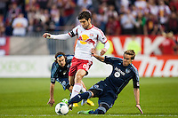 Chance Myers (7) of Sporting Kansas City goes for a tackle on Juninho (8) of the New York Red Bulls. Sporting Kansas City defeated the New York Red Bulls 1-0 during a Major League Soccer (MLS) match at Red Bull Arena in Harrison, NJ, on April 17, 2013.