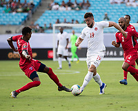 CHARLOTTE, NC - JUNE 23: Lucas Cavallini #19 makes a run on goal while Yosel Piedra #6 defends during a game between Cuba and Canada at Bank of America Stadium on June 23, 2019 in Charlotte, North Carolina.