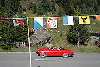 Switzerland. Canton of Ticino. Val di Blenio (Blenio valley). Acquacalda. Swiss german tourists drive their red convertible car up the road of the Lucomagno (Lukmanier) pass. Swiss cantons flags (left to right: Jura, Zürich, Bern, Luzern, Uri) tied on a rope are flying in the wind. © 2006 Didier Ruef