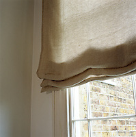 A natural linen blind hangs in the window of a living room