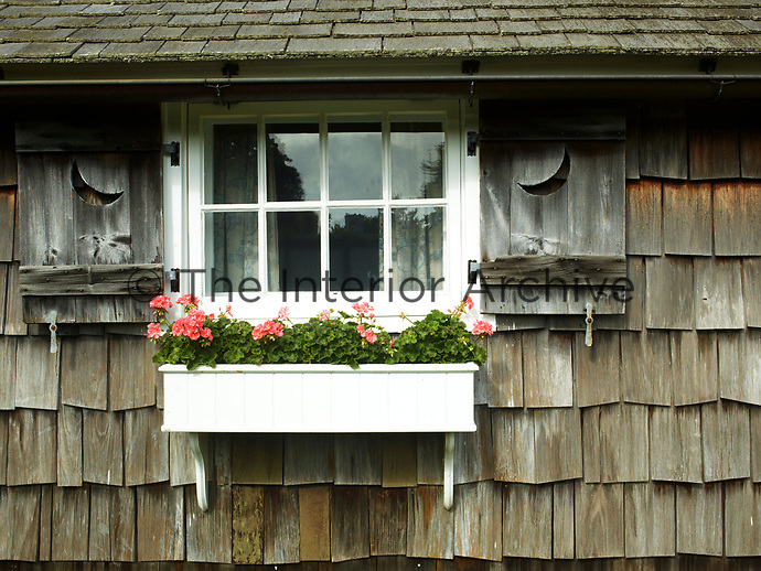 The cottage exterior is faced in lapped clapboard and the window has wooden shutters. A window box is fixed below.